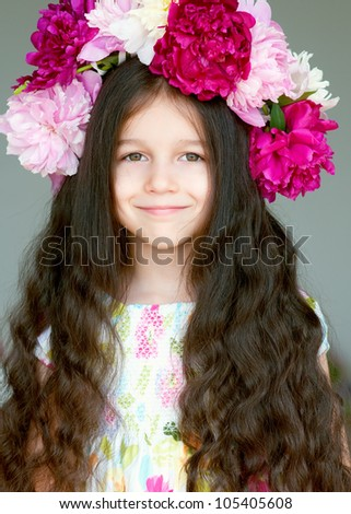 Adorable little girl with wreath from peony flowers in studio. Portrait