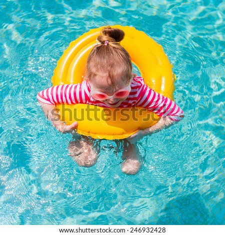 Adorable little girl with yellow inflatable ring swimming in a pool on summer vacation - stock photo