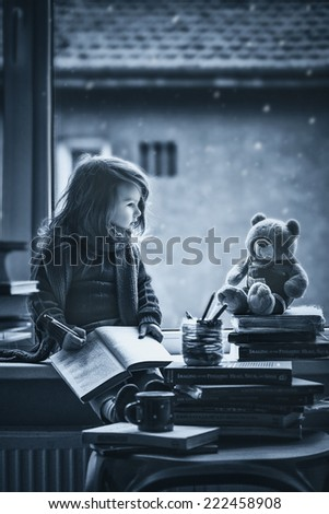 Adorable little girl, writing letter to Santa, sitting on a window, books and teddy bear around - stock photo