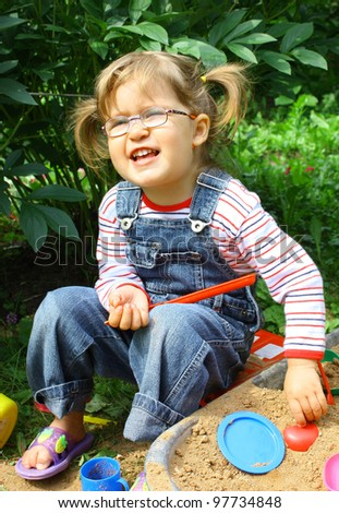 Adorable little girl 2 years old wearing glasses in jeans overalls playing in a sandbox - stock photo