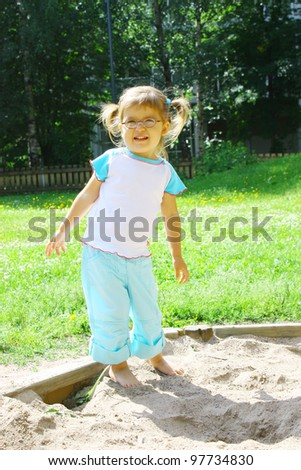 Adorable little girl 2 years old wearing glasses playing in a sandbox - stock photo