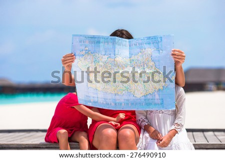 Adorable little girls and mom with map of island on beach - stock photo