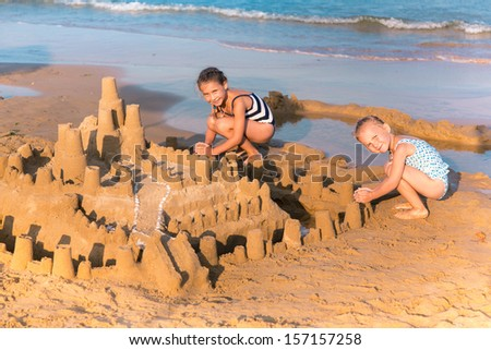 Adorable little girls building a sandcastlle at the seashore