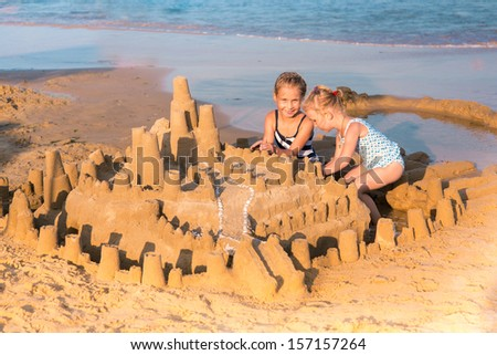 Adorable little girls building a sandcastlle at the seashore - stock photo