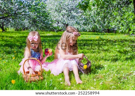 Adorable little girls have fun in blossoming apple tree garden at may - stock photo