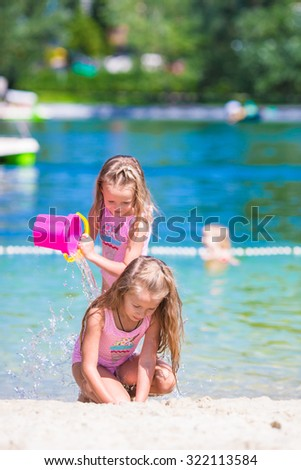 Adorable little girls having fun during beach vacation - stock photo
