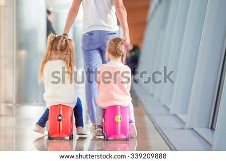 Adorable little girls in airport sitting on suitcase waiting for boarding - stock photo