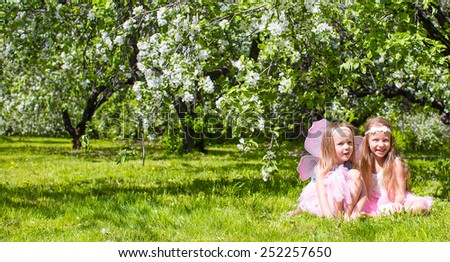 Adorable little girls in blossoming apple tree garden at spring day - stock photo