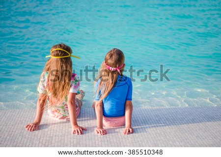 Adorable little girls in outdoor swimming pool - stock photo
