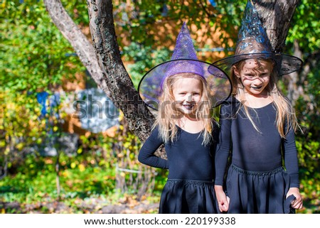 Adorable little girls in witch costume on Halloween outdoors