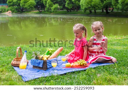 Adorable little girls picnicing in the park at sunny day