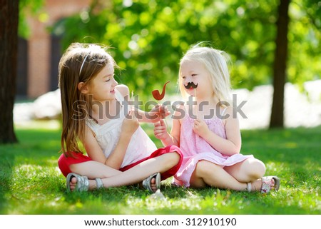 Adorable little girls playing with paper moustaches on a stick and other party accessories - stock photo