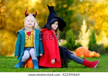 Adorable little girls wearing halloween costume having fun on a pumpkin patch on beautiful autumn day - stock photo