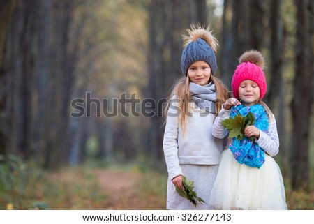 Adorable little girls with autumn leaves in the beautiful park