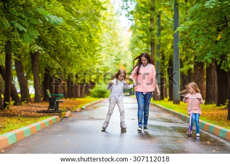 Adorable little girls with happy mom have fun on the scooter outdoor - stock photo