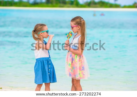 Adorable little girls with lollipop on tropical beach - stock photo