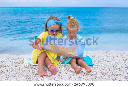 Adorable little girls with map of island on tropical beach - stock photo