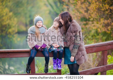 Adorable little girls with mother in autumn park outdoors. Family of three enjoy warm day - stock photo