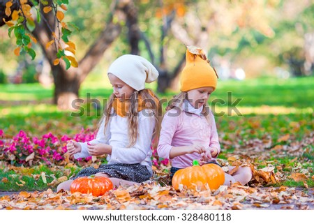 Adorable little girls with pumpkins outdoors at beautiful autumn day. Trick or treat