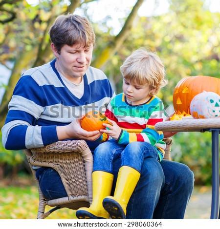 Adorable little kid boy and his dad making jack-o-lantern for halloween in autumn garden, outdoors. Family having fun together and celebrating thanksgiving. - stock photo