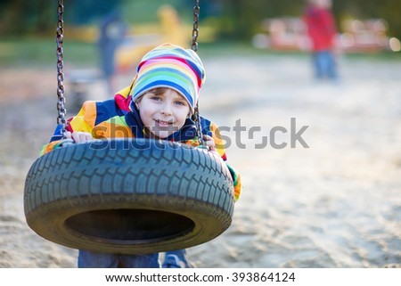 Adorable little kid boy having fun with chain swing on outdoor playground. child swinging on warm sunny spring or autumn day. Active leisure with kids. Boy wearing colorful clothes - stock photo