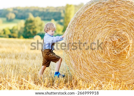 Adorable little kid boy having fun with hay stack on wheat field on warm summer evening. - stock photo