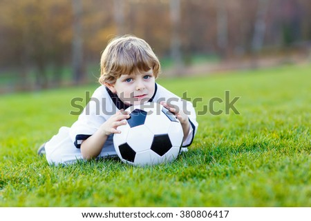 Adorable little kid boy having fun with playing soccer with football on field, outdoors. In white German national uniform. Happy child about european championship