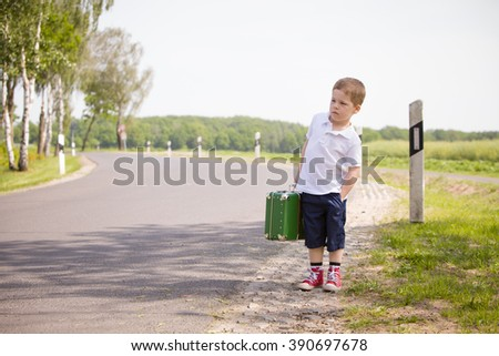Adorable little kid boy in a white polo shirt and shorts holds a green retro suitcase and  stands on the countryside road waiting for a bus or a car. Ready for travel. Vacation time. Child on the road - stock photo