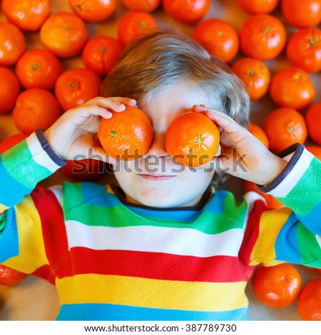 Adorable little kid boy in colorful clothes with mandarin oranges background. Happy smiling child having fun with lot of fruits. Healthy food, eating and lifestyle concept. - stock photo