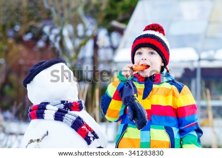 Adorable little kid boy making a snowman and eating carrot. child playing and having fun with snow on cold day. Active outdoors leisure with kids in winter. - stock photo
