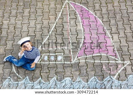 Adorable little kid boy playing with colorful chalks and painting ship or boat picture. Creative leisure for children outdoors in summer, Family, happy childhood,  kids concept - stock photo