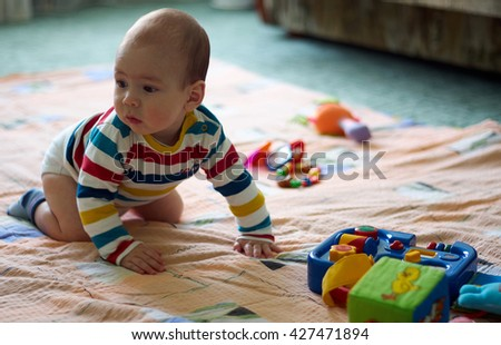 Adorable Little kid boy playing with lots of colorful toys indoor. Active baby boy having fun. Lifestyle, childhood, People, nursery concept/Cute baby in striped shirt playing in the child's room - stock photo