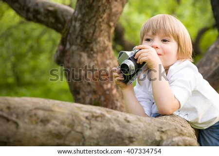 Adorable little kid boy sitting on the old tree and taking picture with the retro photo camera. Child making photo in the summer park. Outdoors. - stock photo