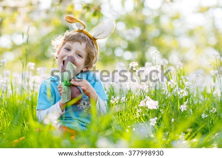 Adorable little kid boy wearing Easter bunny ears celebrating traditional feast. Funny child  eating chocolate figure on sunny day. Family, holiday, spring , carefree childhood concept. - stock photo