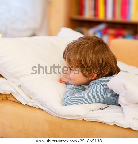 Adorable little kid boy with blond hairs looking on Christmas tree lights and dreaming. Child waiting for Christmas. - stock photo