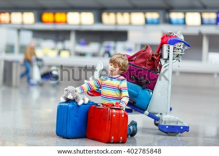 Adorable little kid boy with colorful suitcases and toy on international airport. Happy child waiting for flight and going on vacations. - stock photo