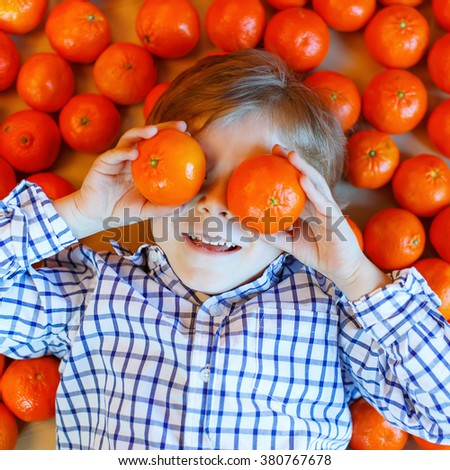 Adorable little kid boy with mandarin oranges background. Happy smiling child having fun with lot of fruits. Healthy food, eating and lifestyle concept. - stock photo