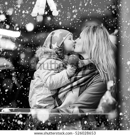 Adorable little kid daughter and young mother eating crystallized sugared apple on German Christmas market. Happy family, girl and woman in winter clothes with lights, Black white picture.