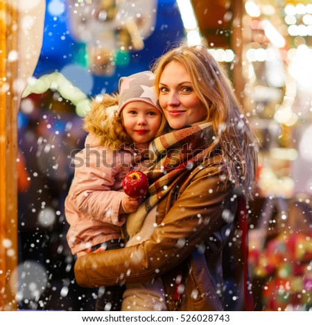 Adorable little kid daughter and young mother eating crystallized sugared apple on German Christmas market. Happy family, girl and woman in winter clothes with lights on background.