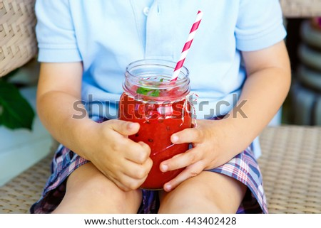 Adorable little kid  drinking healthy fruits and vegetables juice smoothie in summer. Hands of child with drink.