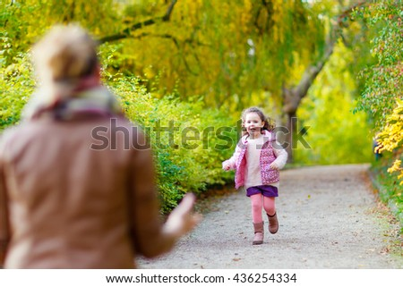 Adorable little kid girl and young woman in beautiful autumn forest. Daughter running to mother. Family portrait, fall season.