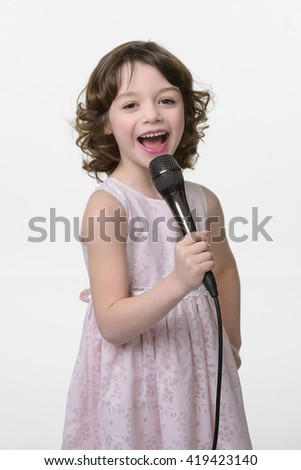 Adorable little kid sings a song in the microphone in her hands. Beautiful kid shows her sincere emotions of happiness and positive. Curled hair and cute pastel dress. - stock photo