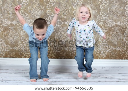 Adorable little kids jumping in air in studio - stock photo