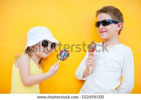 Adorable little kids with colorful lollipops