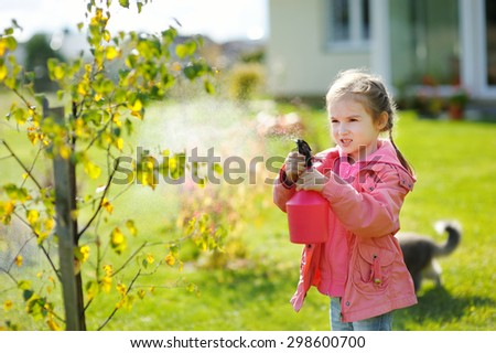 Adorable little mommy's helper watering plants in the garden on beautiful autumn day