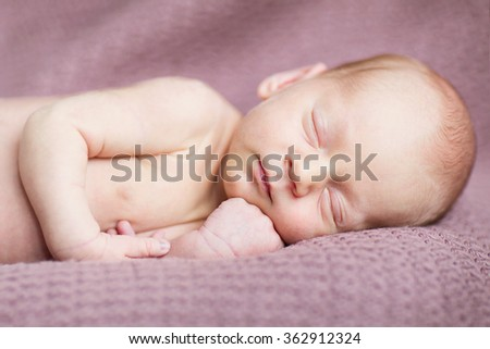adorable little newborn boy lying on the brown blanket - stock photo