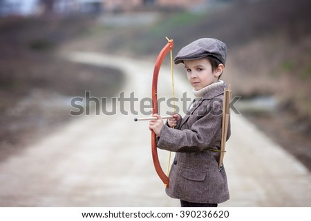 Adorable little preschool boy, shoot with bow and arrow at target in open air, springtime outdoors - stock photo