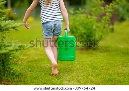 Adorable little preschooler girl watering flowers and plants in the garden - stock photo