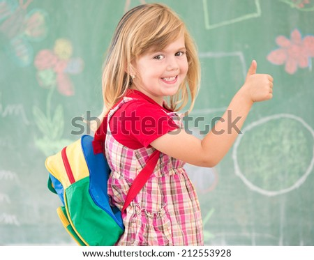 Adorable little school blonde girl in school classroom on board posing with backpack - stock photo