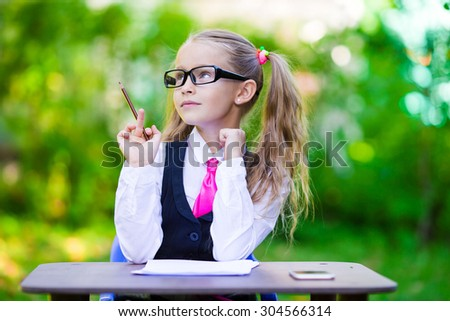 Adorable little school girl at a table with notes and pencils, back to school outdoors - stock photo